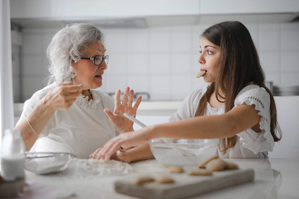 pensive grandmother with granddaughter having interesting conversation while cooking together in light modern kitchen